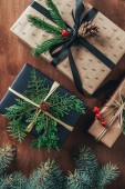 top view of christmas gift boxes with fir branches and pine cones on wooden background