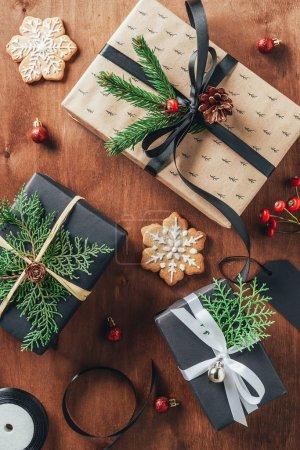 Foto de Endecha plana con regalos, bolas de Navidad, ramas de abeto y cookies sobre fondo de madera - Imagen libre de derechos