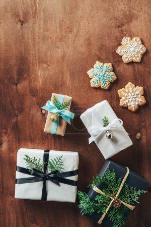 Foto de Vista superior de cajas de regalo de Navidad y las galletas de copo de nieve sobre fondo de madera - Imagen libre de derechos