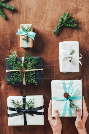 cropped view of woman holding christmas gifts with fir tree branches on wooden background