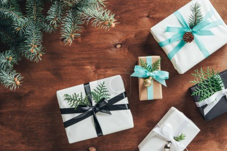 top view of christmas gift boxes with fir tree branches and decoration on wooden background