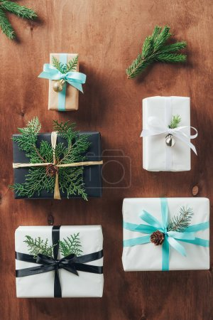 top view of christmas gifts decorated with fir branches and ribbon bows on wooden background