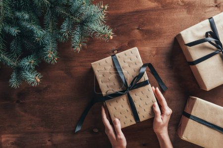 partial view of woman holding christmas gifts on wooden background with fir tree branches