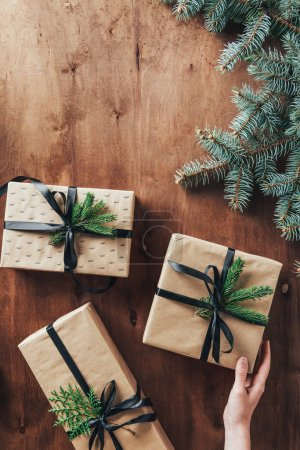 cropped view of woman touching gift boxes on wooden background with christmas tree branches