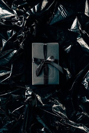 top view of gift box with black ribbon on black wrapping paper backdrop
