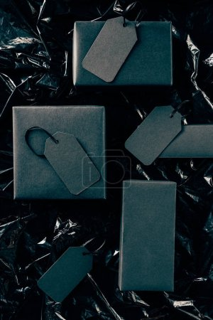 flat lay with black boxes with blank price tags on black wrapping paper backdrop, black friday concept