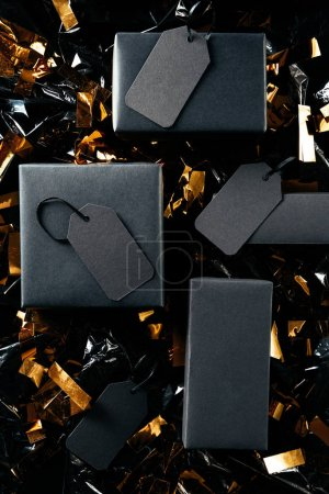 flat lay with black boxes with blank price tags and golden confetti on black wrapping paper backdrop, black friday concept