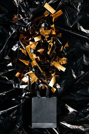 top view of paper shopping bag with golden confetti on black wrapping paper backdrop, black friday concept