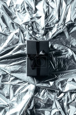 top view of gift box with black ribbon on silver wrapping paper backdrop