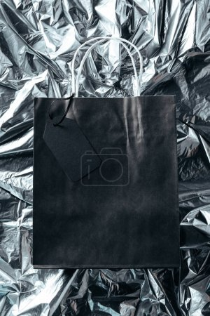 top view of black paper bag with blank price tag on silver wrapping paper background, black friday concept