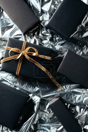 flat lay with arranged gift with golden ribbon and blank black boxes on silver wrapping paper background
