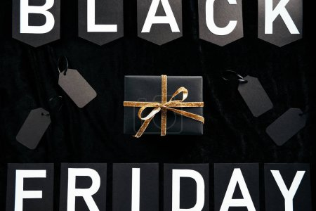 top view of black friday lettering, wrapped gift and blank price tags on black backdrop