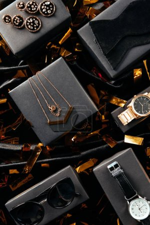 Photo for Flat lay with feminine shoes, purse and jewelry on black background with golden confetti - Royalty Free Image
