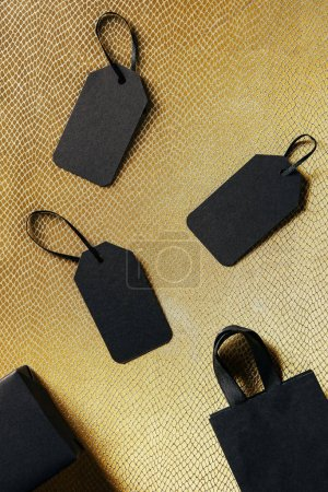 Photo for Top view of black blank price tags, box and shopping bag on golden backdrop, black friday concept - Royalty Free Image