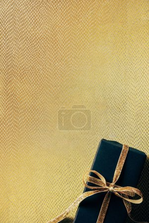 top view of wrapped gift box with golden ribbon on golden background