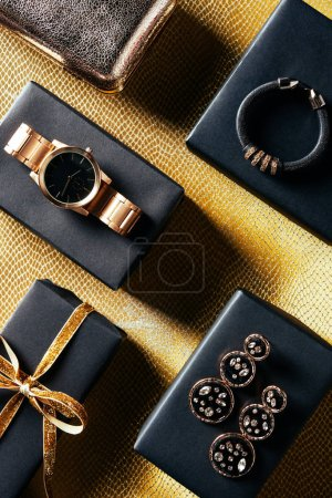 flat lay with wrapped gift, feminine jewelry and purse on golden backdrop
