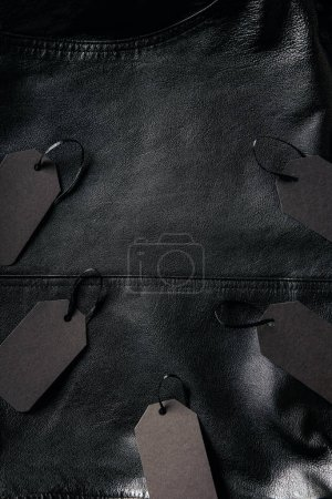 top view of arranged blank price tags on black leather jacket background, black friday concept