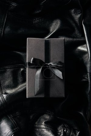 top view of black wrapped gift on black leather jacket background