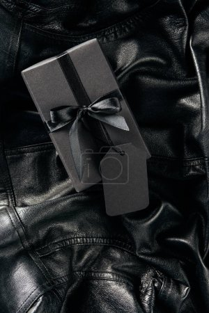 top view of black wrapped gift with blank price tag on black leather jacket background, black friday concept