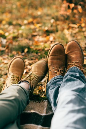 camera point of view on two pairs of orange boots in beautiful foliage in autumn