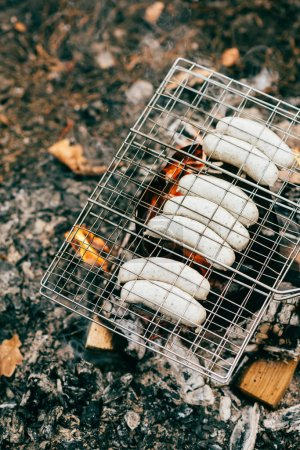 top view on row of sausages roasting on grill grate over fire