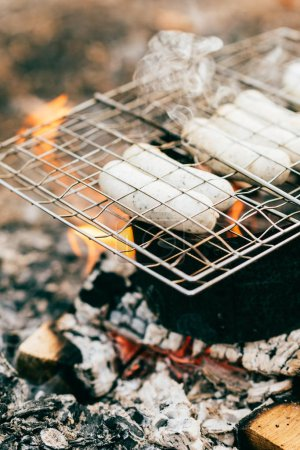 row of sausages roasting on grill grate over fire outdoors