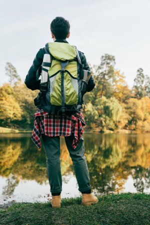 rear view of traveller with backpack on autumnal background