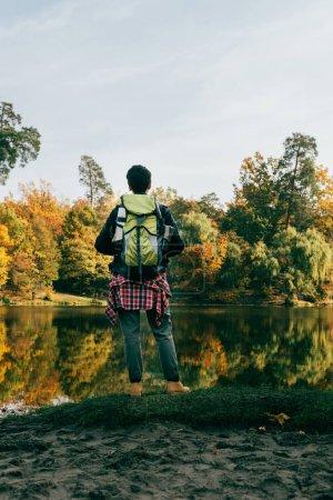 Photo pour Vue arrière du voyageur avec sac à dos sur fond automnal - image libre de droit
