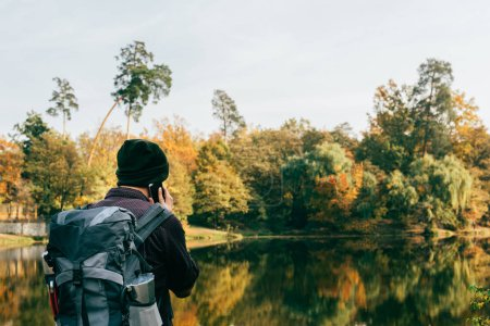male traveller with backpack on autumnal background