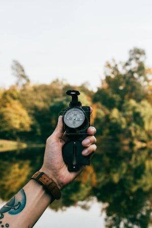 hand of man holding compass on autumnal background