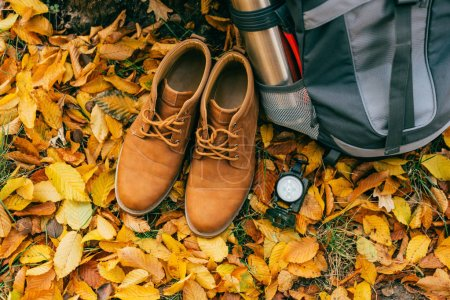 top view on camping supplies and orange boots on beautiful autumn foliage