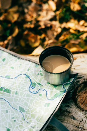 coffee in metallic thermos cup on travel map