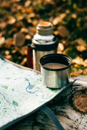 coffee in metallic thermos cup on travel map on blurred autumnal background