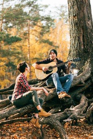 Photo pour Femme heureuse et l'homme s'amuser avec la guitare sur fond d'autumal - image libre de droit