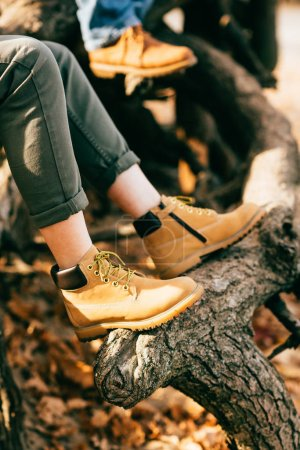 Photo pour Personne qui porte des bottes orange sur fond de feuillage automne - image libre de droit