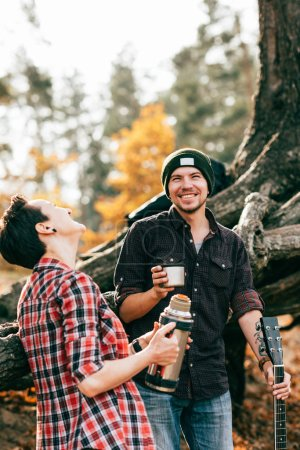 adult couple laughing and having tea on autumal background