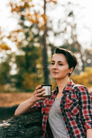 Photo for Adult woman holding metallic thermos cup on blurred autumnal background - Royalty Free Image