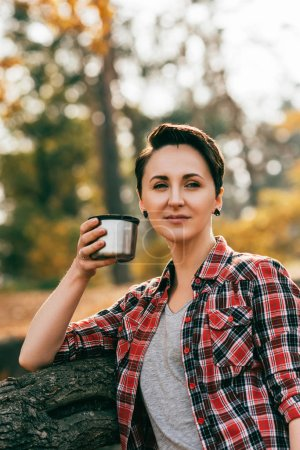 Photo for Adult woman looking at camera hoding metallic thermos cup on blurred autumnal background - Royalty Free Image