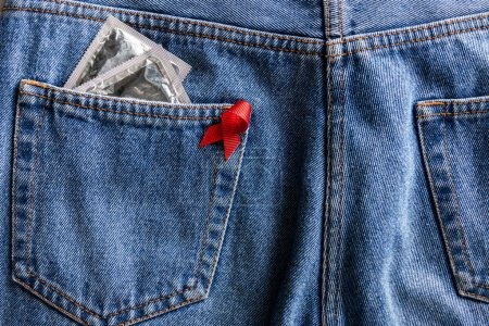 aids awareness red ribbon and silver condoms in pocket of blue jeans