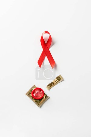 top view of aids awareness red ribbon and red condom with golden packaging on white background