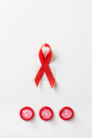 top view of aids awareness red ribbon and red condoms on white background