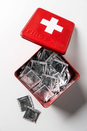 top view of first aid kit red box with silver condoms isolated on white