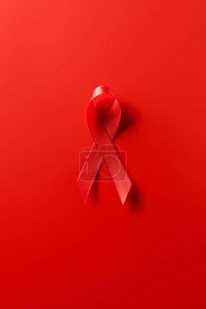 Photo pour Vue du dessus du ruban rouge de sensibilisation aux aides sur fond rouge - image libre de droit