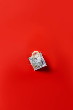 top view of condom in silver packaging on red background