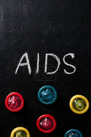 top view of aids sign with multicolored condoms on black background