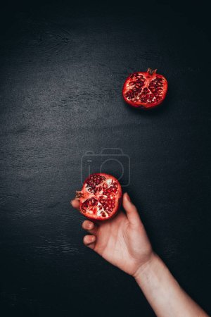 Photo for Partial view of female hand and cut pomegranate on black tabletop - Royalty Free Image