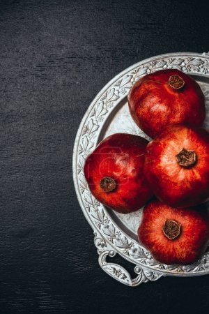 flat lay with fresh pomegranates on metal serving tray on black tabletop