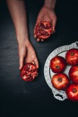 partial view of woman holding pomegranate halves on black surface with metal tray