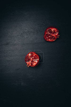 top view of pomegranate halves on black surface