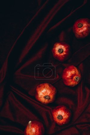 flat lay with fresh pomegranates on red velvet cloth backdrop